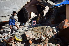 Young man walking pass collapsed building after earthquake disaster Stock Photos