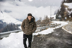 Young man walking on roadside under the snow Stock Photography