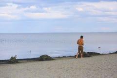 Young man walking on sand beach Stock Photos