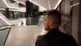 Young man walking in a shopping center. A young man is walking in a shopping center stock video footage