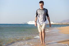 Young man walking on the shoreline royalty free stock photography