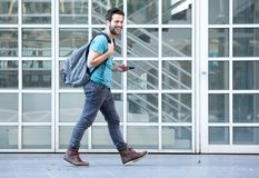 Young man walking on sidewalk with mobile phone and bag. Side view portrait of a young man walking on sidewalk with mobile phone and bag Stock Photos
