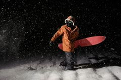Young man walking with the snowboard in the mountain resort in t royalty free stock image