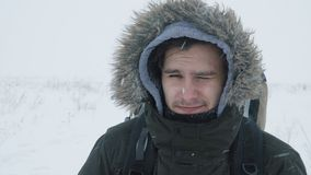 Young man walking through a snowstorm. A portrait of a young man with backpack during snowstorm in the snowy wilderness, struggling wind and extreme cold stock video