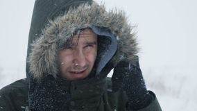 Young man walking through a snowstorm. A portrait of a young man during snowstorm in the snowy wilderness, giving thumb up stock footage