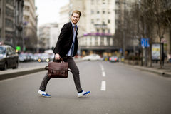Young man walking on the street. Young man walking across the street Royalty Free Stock Photo