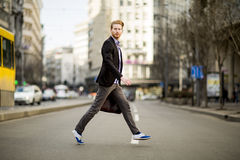 Young man walking on the street Stock Photos