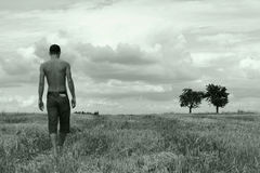 Young man walking on a stubble-field