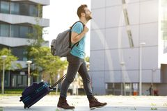 Young man walking with suitcase and bag Stock Photography
