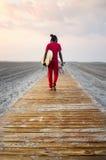 Young man walking towards seaside with surfboard. Young man walking towards seaside with a surfboard Stock Photos