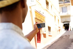 Young man walking in town taking selfie Royalty Free Stock Images