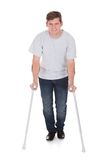 Young Man Walking With Two Crutches Stock Image
