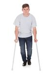 Young man walking with two crutches Royalty Free Stock Photo