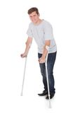 Young man walking with two crutches Stock Photo