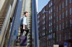 Young man walking up escalator with travel bags Royalty Free Stock Photos