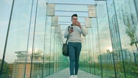 A Young Man Walking and Using a Phone. A young man walking and using a smartphone in a glass corridor. Dolly shot. Long shot Royalty Free Stock Photos