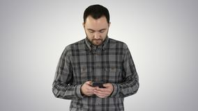 Young man walking and using a smartphone on gradient background. royalty free stock photos