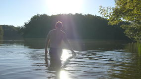 Young man walking in water at river at summertime. Rear back view stock video