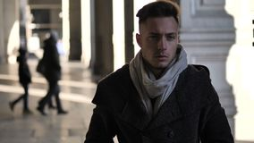Young man walking and wearing scarf under colonnade. In Turin, Italy, in a typical European city setting stock video footage