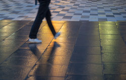 Young man walking on wet pavement Stock Image