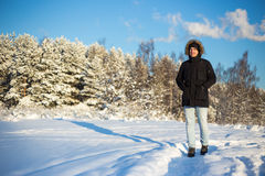 Young man walking in winter forest Stock Photo