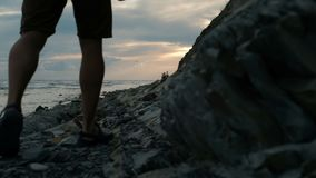 Young man walks along beach in late summer evening outdoors. stock video footage