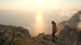 Young man walks along the edge of a cliff observing beautiful dramatic colorful sunset above a sea from a high mountain. Young man arms outstretched observes a stock footage