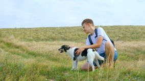 A young man walks with a dog along the sea coast. stock footage