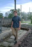 Young man walks down a stone tiled path stock photo