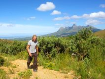 Young man walks on road. And amazing mountains as a background. Shot in Hottentots Holland Mountains, Vergelegen area, near Somerset West, Western Cape, South Stock Images