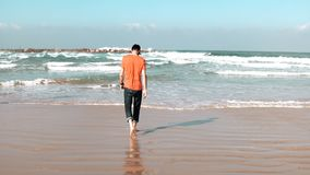 Young man walks on summer sea beach, throws stone. Freedom and retreat concept. Thinking about life. Big foam waves. 4K. Young man in orange t-shirt walks on stock video