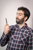 Young man want comb his beard and moustaches Royalty Free Stock Photo