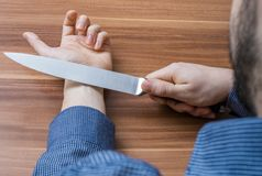 Young man wants to commit suicide by cutting vein on hand with knife.  Royalty Free Stock Photos