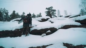 Young man climbing rocky cliff side covered in snow. Young man in warm clothes and backpack climbing rocky cliff side covered in snow on cold cloudy winter day stock video