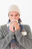 Young man in warm clothing sneezing Royalty Free Stock Images