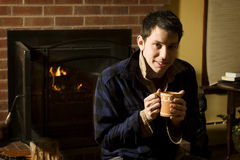 Young man warming up by fire Royalty Free Stock Photos
