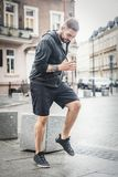 Young man warming up on the street. Stock Images