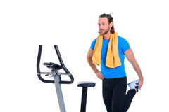 Young man warming up for train with fitness machine. Young man in blue shirt warming up for train with fitness machine stock photography