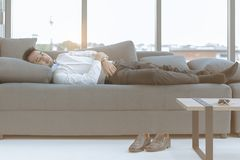 The young man was sleeping on a large sofa comfortably. in luxurious room, there is a smartphone on the table and shoe on the fro royalty free stock photography