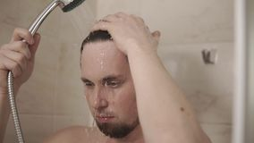 Portrait of a young man who is washing in the shower under a mixer. A young man washes in the bathroom under the shower, the gentleman holds the mixer by hand stock video