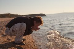 Young man washes himself in Lake Baikal Stock Photos