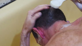 Young Man Washes his Head with Shampoo under the Shower stock video footage