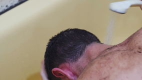 Young Man Washes his Head under the Shower. stock footage