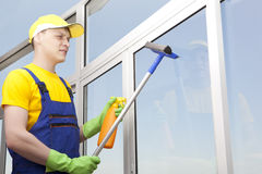 Young man washes window Royalty Free Stock Photo