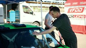 Young man washes the windshield of a green sports car for street racing drift stock video