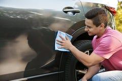 Young man washing car door with rag stock photos