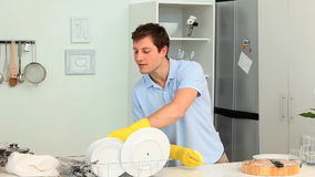 Young man washing dishes stock footage