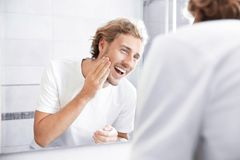 Young man washing face with soap near mirror. In bathroom stock photography