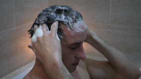 Young man washing hair with shampoo, massaging the foam head, slow motion stock footage