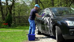 Young man washing his black car with soapy sponge. stock footage